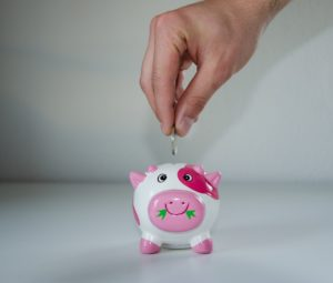 Coin being put into a piggy bank